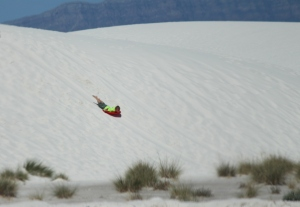 Kids sliding down the sand dunes with sleds bought at the visitor center.